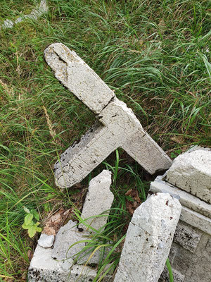 Verfallene Betonkreuze des ehemaligen Friedhofs. Die Gefallenen wurden direkt nach dem Krieg umgebettet.