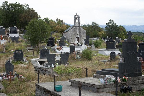 9.9. Unterwegs kommen wir an einem Friedhof vorbei. Auf den Gräbern fallen kleine Glaspyramiden auf, die Plastikblumen enthalten.