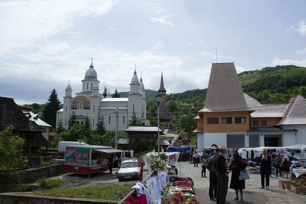 """18.6. Botiza - Gleich neben der traditionellen Holzkirche  bildet die moderne Allerheiligenkirche / Biserica nouă """"Duminica tuturor sfinților"""" einen starken Kontrast."""