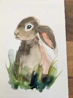 Ausarbeitungen: Das Auge (bitte einen Lichtreflex aussparen) und das Schnäuzchen mit einem feinen Pinsel malen.  Jetzt sitzt das Häschen im Gras, das auch locker mit dickem Pinsel gelbgrün + etwas Indigo angelegt ist.