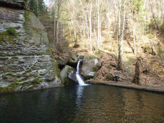 Ein kleiner Wasserfall speist das Rückhaltebecken, das von gigantischen Felswänden umgeben ist.