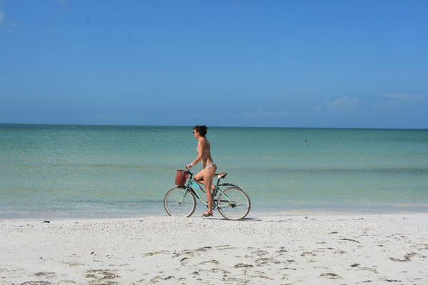 Eine Frau und ein Fahrrad auf dem Strand