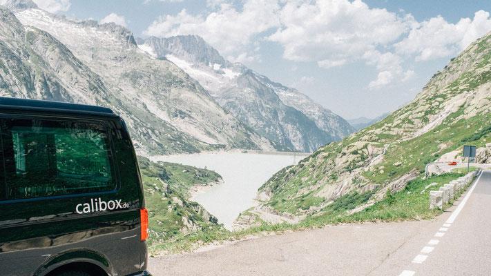 VW-Bus mit Blick über die Alpen