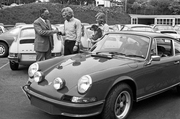 Uli Hoeneß (Mitte) nimmt seinen Porsche 911 Carrera RS 2,7 Coupé (Mj. 1973) entgegen; links Harald Wagner.