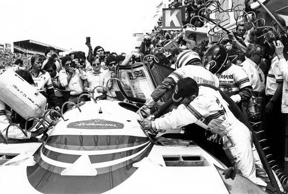 Le Mans 1982: Porsche 956 LH bei einem Boxenstopp, mit gestreiftem Helm Derek Bell, rechts neben ihm Jacky Ickx, hinter dem Sicherheitsbehälter beim Tanken Rennmechaniker Gerhard Küchle