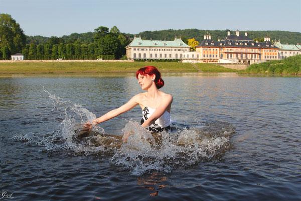 Braut badet in der Elbe im Brautkleid