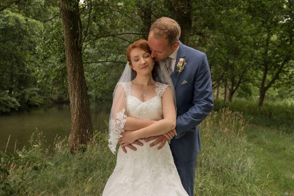 Das Brautpaar beim Fotoshooting - Bräutigam umarmt Braut