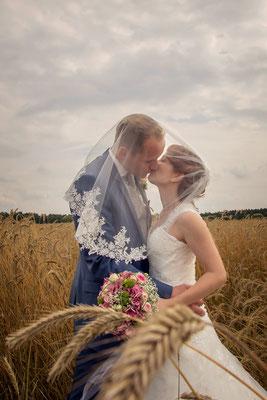 Das Brautpaar unter dem Brautschleier - Kuss