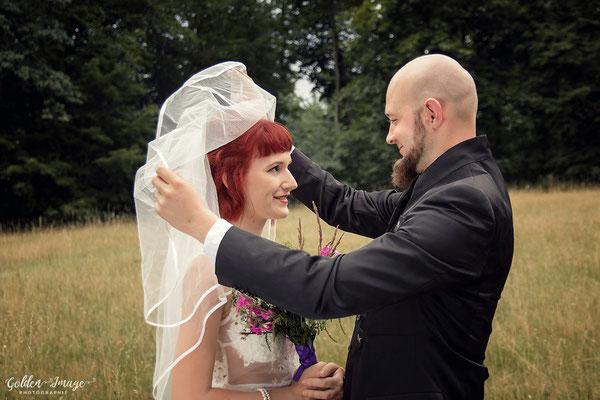 Bräutigam hebt den Schleier der Braut hoch
