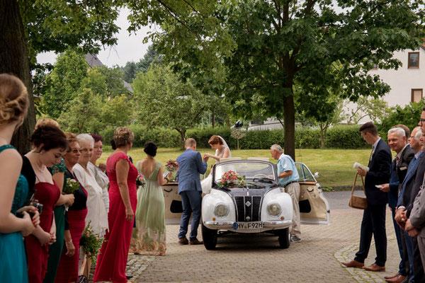 Das Brautpaar steigt aus dem Brautauto vor der Kirche in Oßling