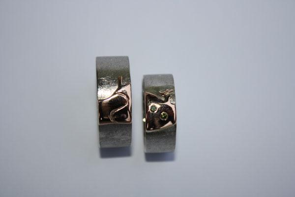(05) Eheringe aus Palladium und Rotgold mit dem Motiv des Geisingberges und grünem Diamant.