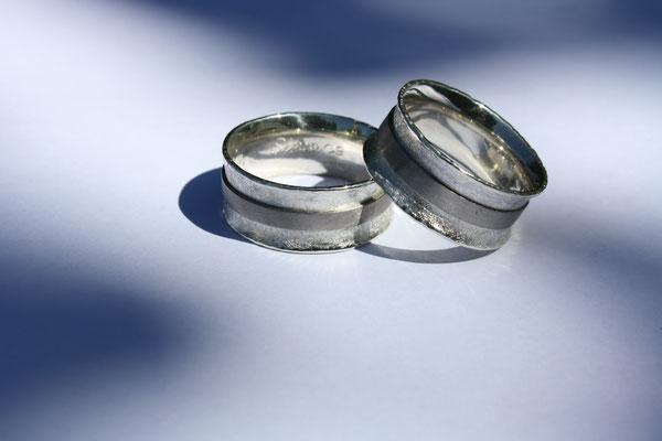 (07) Eheringe aus Silber mit Palladiumstreifen besetzt. Sehr breite Eheringe. Trauringe konkav gewölbt.