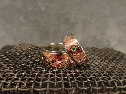 (02) Eheringe aus Silber innen und Rotgold außen. Hammerschlag Oberfläche. Granat und grüner Zirkonia. Sehr breite Trauringe