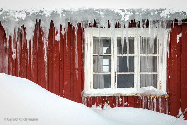 Eiszapfen an einem typischen Holzhaus