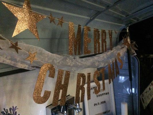 """Eine Girlande in der mobilen Sektbar mit der Schrift """"Merry Christmas"""""""