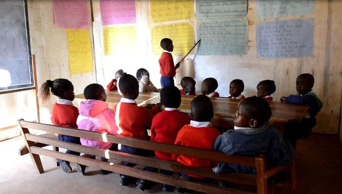 Ein Kind ließt seinen Mitschülern vor und diese wiederholen das Gesprochene
