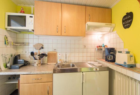 Eine komplett eingerichtete Küche mit Mikrowelle, Kaffeemaschine, Brotschneider, 2-Platten-Elektroherd, Kühlschrank, Toaster, etc.
