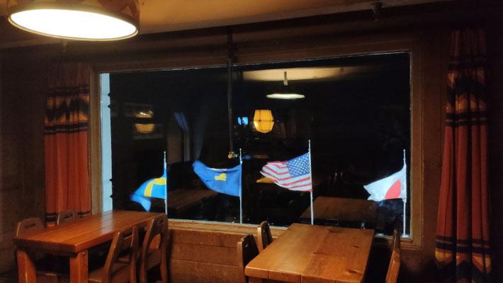 Vor dem Haus wehen die Fahnen von Nationen, die hier regelmäßig Skitraining machen