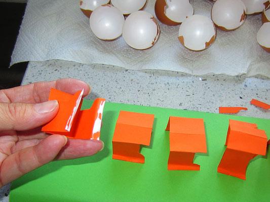 die füßchen am ende etwas umbiegen, sodass der kleber darauf befestigt werden kann; auf die unterlage aufkleben; vorher noch so biegen, sodass die eierschalenhälfte gut aufgeklebt werden kann
