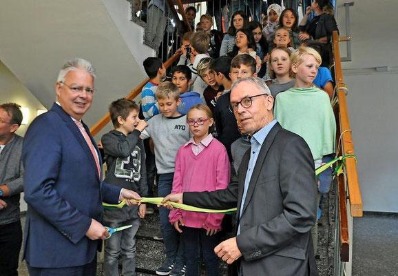 Lehrtes Bürgermeister Klaus Sidortschuk und IGS-Leiter Bernhard Mellentin schneiden gemeinsam das Band am Treppenaufgang zum neuen Freizeitbereich durch. Quelle: Katja Eggers