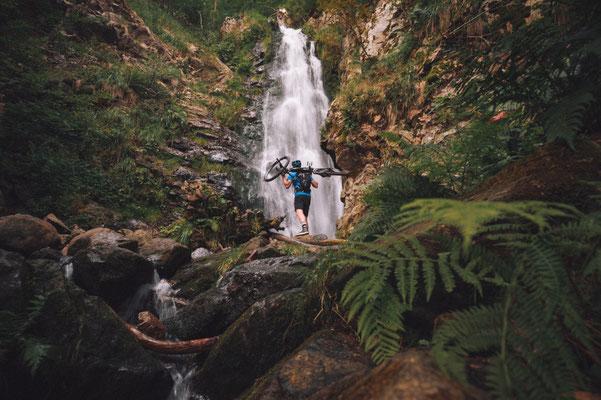 Mann mit dem Cannondale Trail Neo auf der Schulter an einem Wasserfall
