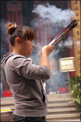 A devotee burning incense at the Jade Buddha Temple, Shanghai