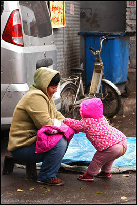 "A sight of the practical ""free discharge system"" of the childrens' cloths, in front of the Sihuan Market, Beijing"