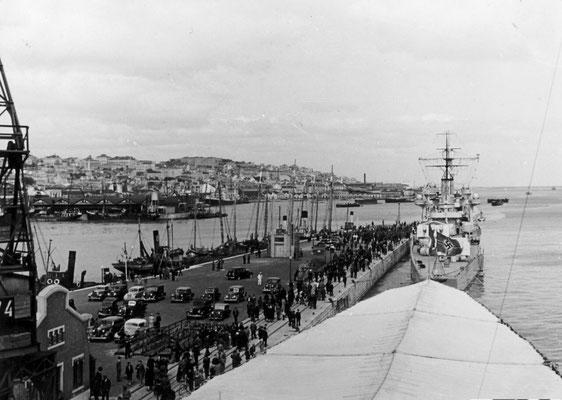 """Der Hafen von Lissabon - die """"Graf Spee"""", für das Boordfest mit abgedeckten Bug und vor ihr der Kreuzer """"Köln""""."""