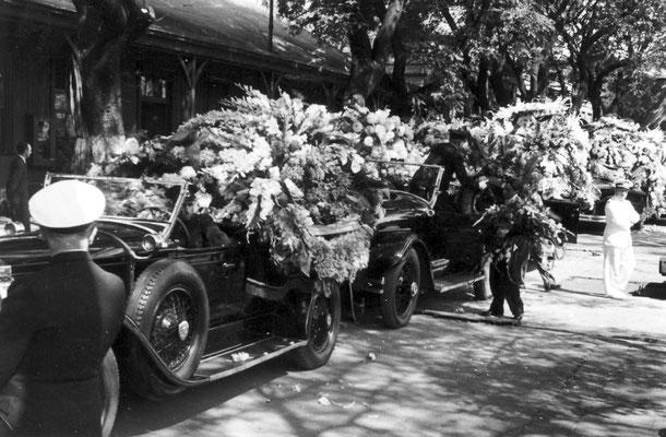 Für diese Kultur typische, mit Blumenkränzen beladene, schwarze Limousinen.