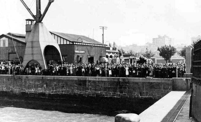 """Argentinier und die """"Deutsche Kolonie"""" beobachten die Ankunft der Deutschen Marinesoldaten gegenüber  der """"Dársena Norte""""."""