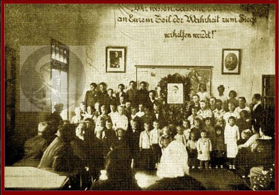 Schulversammlun mit Hitlerbild an der Tafel.