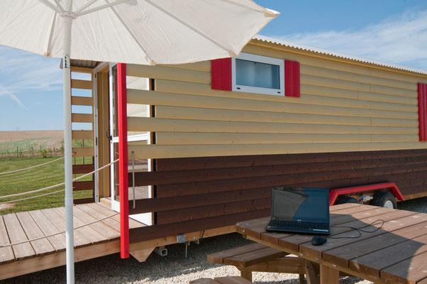 Table de camping, parasol, prise électrique extérieure.