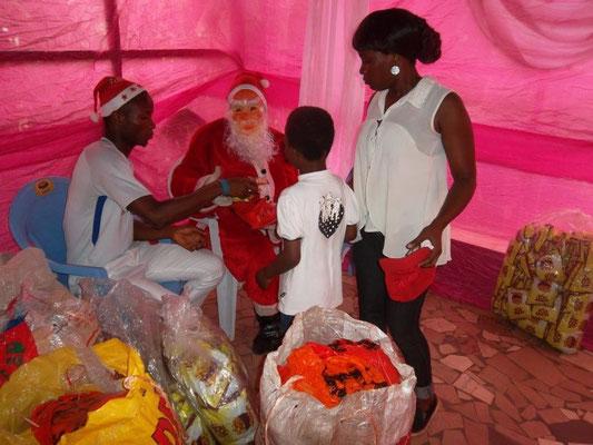 De kerstman deelt de cadeautjes uit.