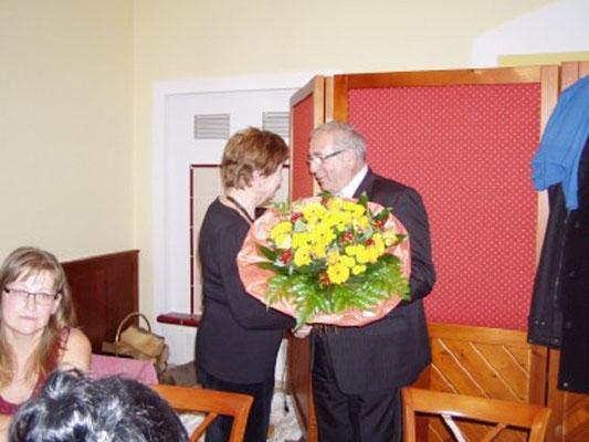Gruppenleiter Pfeiffer bedankt sich mit einem Blumenstrauss bei der Gattin des Jubilars