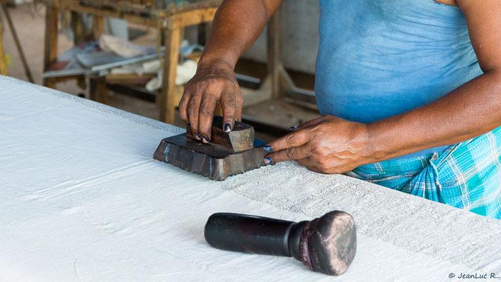 """En frappant le tampon de bois avec le """"marteau"""", l'imprimeur imprègne nettement la couleur dans le tissu."""