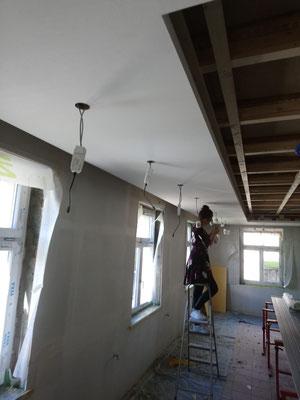 Nach vier Anstrichen sieht die Decke endlich wie gewünscht aus und bereits werden fleissig Lampen installiert (W16)