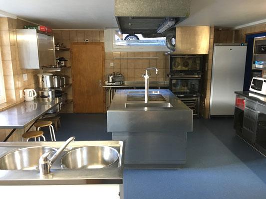 Die umfassend ausgerüstete Küche mit Induktions-Feldern, modernen Öfen und Geschirrspüler ist ideal für Gruppen, die selbst kochen.