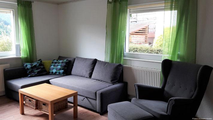 Couch und gemütlicher Sessel im Wohnzimmer