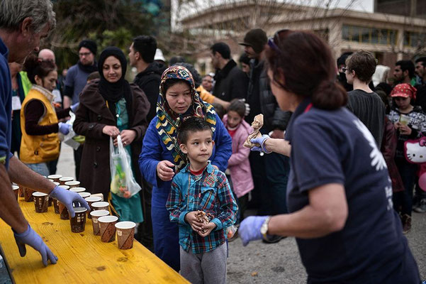 Mitglieder einer NGO verteilen am Hafen Nahrung und Getränke für die Neuankömmlinge. © Louisa Gouliamaki/AFP/Getty Images