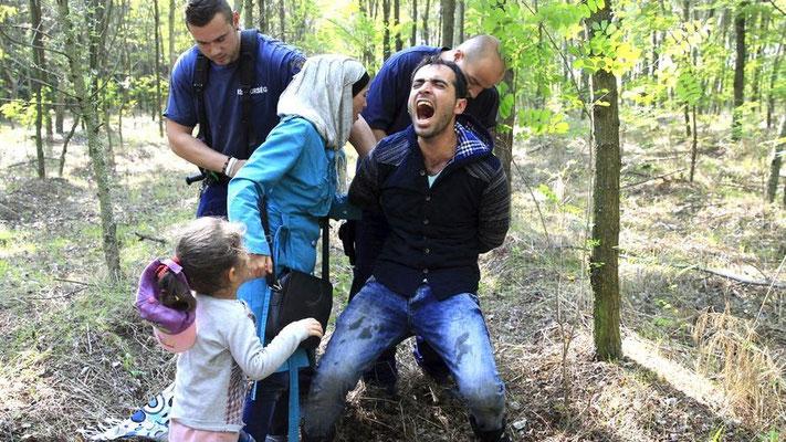 Eine syrische Flüchtlingsfamilie wird von ungarischen Grenzbeamten festgenommen, nachdem sie die Grenze von Serbien nach Ungarn illegal überschritten hatte. © Bernadett Szabo/Reuters