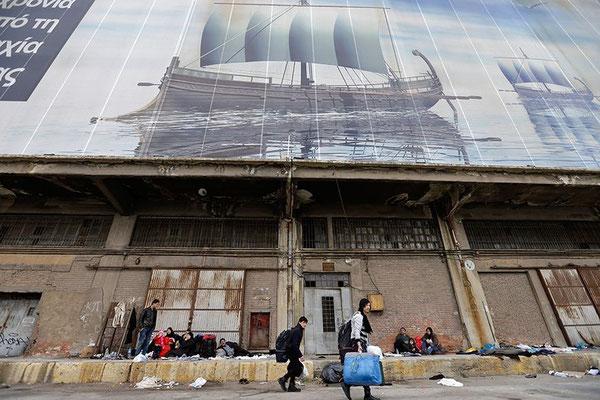 Vor einer alten Lagerhalle auf dem Hafengelände warten Flüchtlinge. Sie wurden von den östlichen griechischen Inseln nach Piräus gebracht. © Thanassis Stavrakis/AP/dpa Auch diese Flüchtlinge warten, wie es weitergeht. Sie rasten vor dem Passagierterminal