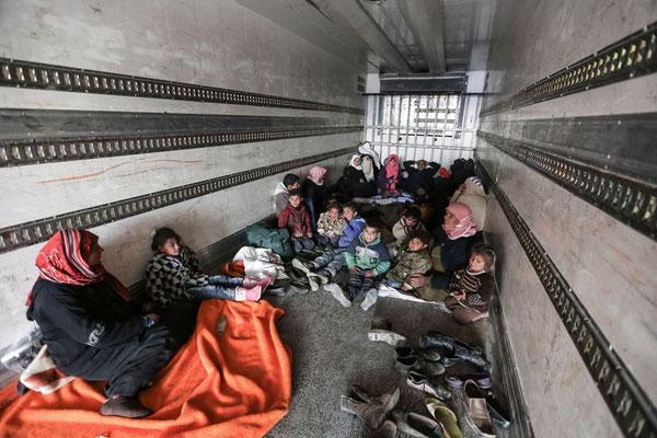 Syrer, die im Grenzgebiet in einem Lastwagen Schutz vor der Kälte suchen © Bunyamin Aygun/dpa