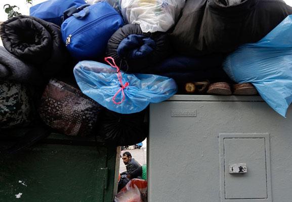 Die meisten Flüchtlinge, die Athen erreichen, gehen zuerst auf den Victoriaplatz. So wie der Mann auf diesem Bild, er trägt ein Bündel Decken auf den Schultern. © Vadim Ghirda/AP/dpa