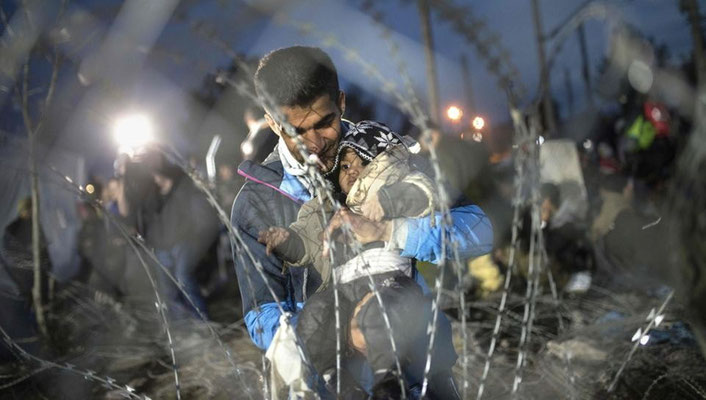 Ein Mann mit seinem Kind an der Grenze Griechenlands zu Mazedonien. Mazedonien sichert die Grenze mit einem Stacheldrahtzaun. | Bildquelle: AFP
