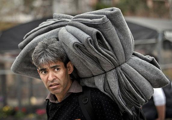 Die meisten Flüchtlinge, die Athen erreichen, gehen zuerst auf den Victoriaplatz. So wie der Mann auf diesem Bild, er trägt ein Bündel Decken auf den Schultern. © Vadim Ghirda/AP/dpa Eine griechische ältere Dame unterhält sich auf dem Victoriaplatz mit ei