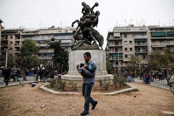 Ein Afghane trägt sein Kind über den Victoriaplatz in Athen. Im Hintergrund eine Statue von Theseus, einem Held der griechischen Mythologie. Er befreite Hippodameia aus der Gewalt des Zentauren Eurytion. © Alkis Konstantinidis/Reuters