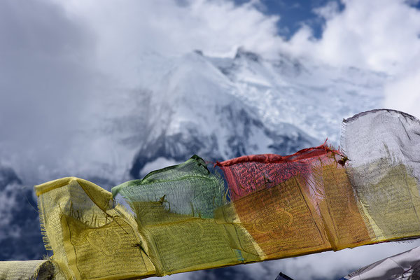 Gebetsfahnen und Bergflanken bei Ghyaru