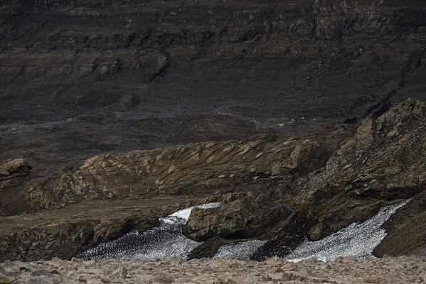 Gesteinsformationen und Restschnee im Kaldidalur