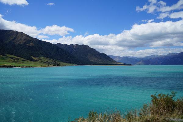 Blick nach links, plötzlich Sonne, blaues Wasser und braune Berge