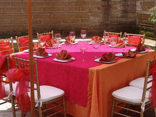 montaje mesa cuadrada bajo mantel naranja cubre mantel fucsia bordado servilletas